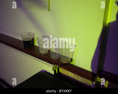 Empty and half empty beer glasses in a London pub - Stock Photo