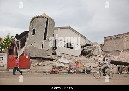 people on the street walking past a collapsed church after the earthquake; port-au-prince, haiti - Stock Photo