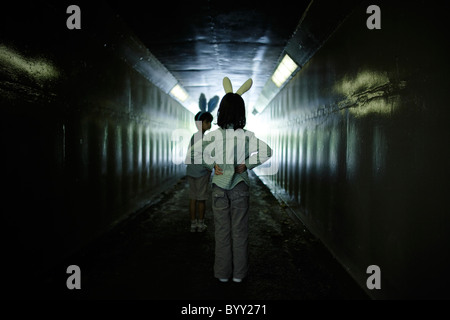 Boy and girl with bunny ears in pedestrian underpass. - Stock Photo