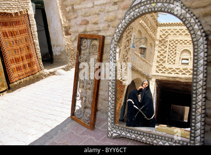Reflection of people in mirror at vendor's shop in the 14th century Ouled El-Hadef (Old Quarter)- Tozeur, Tunisia. - Stock Photo