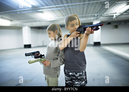 Children with stocking masks and toy guns in underground carpark prepare for big hold-up. - Stock Photo