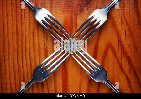 Four forks fighting over one euro coin , financial crisis competition ,wood background - Stock Photo