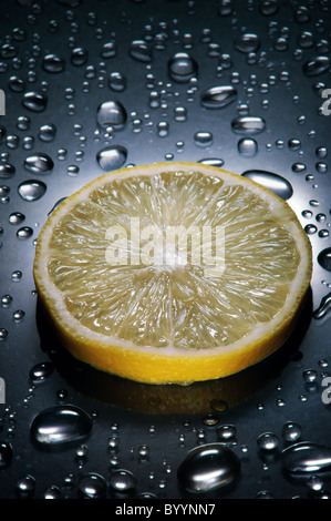 Lemon slice ,  water droplets, dramatic lighting,vertical - Stock Photo