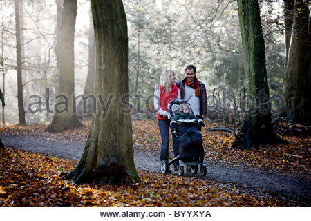 A young couple pushing a stroller in the park, smiling - Stock Photo