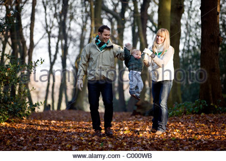 A young couple swinging their son in the air - Stock Photo