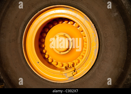 Front loader tyre and yellow wheel rim - Stock Photo