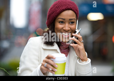 A modern business woman in the city talks on her cell phone while enjoying a cup of coffee. - Stock Photo