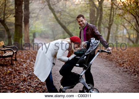 A young couple standing with a stroller in the park - Stock Photo