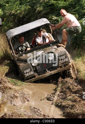 Off road Landrover driving through mud with outside help - Stock Photo