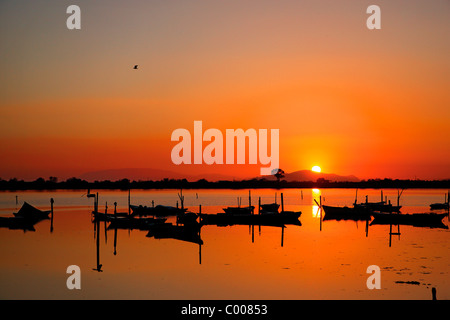 Sunset in the lagoon of Messolonghi with all those beautiful traditional boats, called 'gaitas' in the first plane. - Stock Photo
