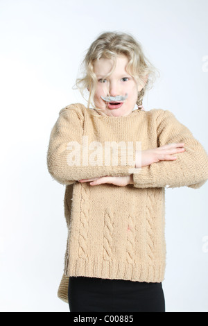 A blond girl with a grey moustache stuck on, leaning back and acting surprised, with arms crossed. - Stock Photo