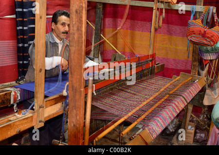 Fast moving weaver operating a horizontal wooden hand loom in a cloth shop Fes el Bali Medina Fez Morocco North - Stock Photo