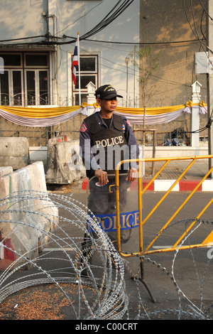 Thai policemen stand guard behind barbed wire during a rally by nationalist 'Yellow Shirts' protesters outside Government - Stock Photo