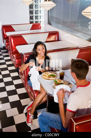 Teen interracial couple having lunch in a retro diner - Stock Photo