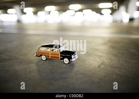 Toy car in empty car park. - Stock Photo