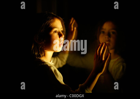Girl at night with window reflection - Stock Photo