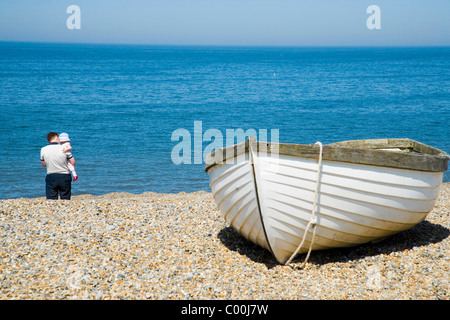 Father and baby behind small fishing boat on beach - Stock Photo