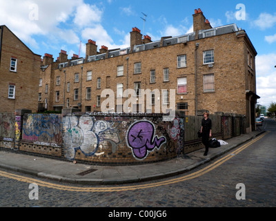 A young man in black walking at the back of a row terraced houses on Grimsby St. near Brick Lane, East End, London - Stock Photo
