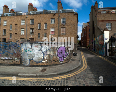 The back of a row of terraced houses and graffiti on a curved brick wall street corner near Brick Lane  Grimsby - Stock Photo