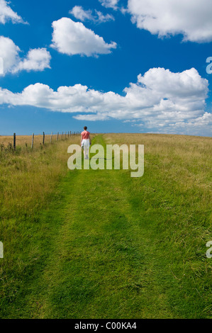 Woman walking along track through South Downs between Lewes and Brighton - Stock Photo