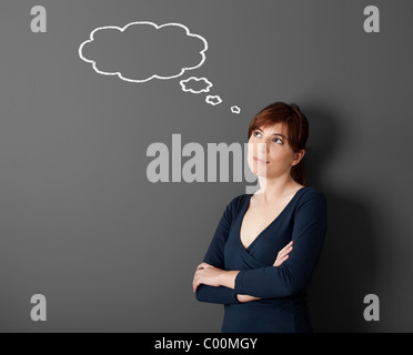 Young woman thinking with a thought a balloon drawn with chalk on the wall - Stock Photo
