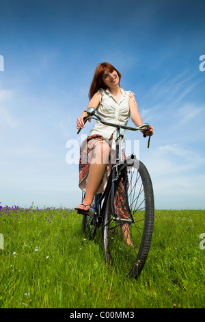 Happy young woman on a green meadow with a vintage bicycle - Stock Photo