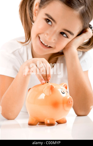 Little girl lying on floor and inserting a one euro coin on the piggy-bank - Stock Photo