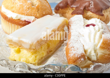 Close up of afternoon tea cream cakes selection. - Stock Photo