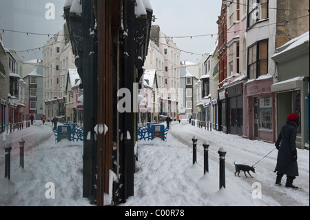 A woman walks her dog along snow covered George Street Old Town Hastings East Sussex England UK - Stock Photo