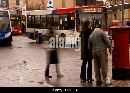Pedestrians standing in the rain at a Royal Mail post box posting letters close to the city centre bus terminal - Stock Photo