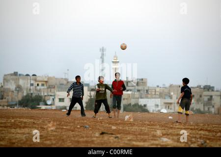 Children playing football in Madaba, Jordan. - Stock Photo