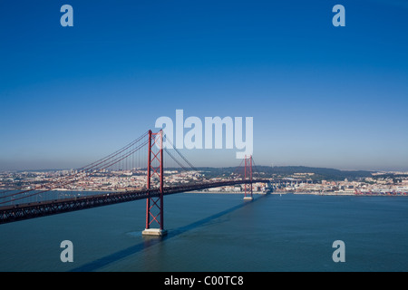 25th of April Bridge over Tagus River, built 1966, Lisbon, Portugal on other side - Stock Photo