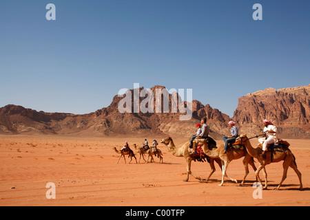 Tourists riding camels in the desert, Wadi Rum, Jordan. - Stock Photo