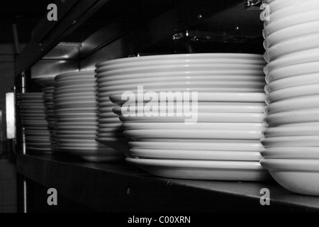 stacked plates on shelf in kitchen - Stock Photo