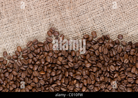 Background image of many coffee beans spilled out on a canvas material - Stock Photo