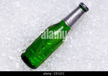 Photo of a green glass bottle of beer on crushed ice. - Stock Photo