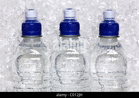 Photo of cold mineral water in plastic bottles on crushed ice - Stock Photo