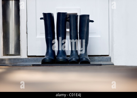 Two pairs of Wellington boots by a door - Stock Photo