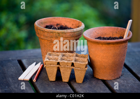 Terracotta plant pots and seed trays on a garden table - Stock Photo