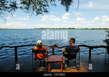 Tourists sitting on the terrace of a lodge on the Guma Lagoon, Okavango Delta, Botswana, Africa - Stock Photo