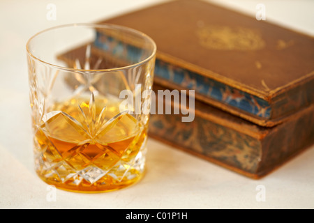 Glass of  malt whisky and old antique books - Stock Photo