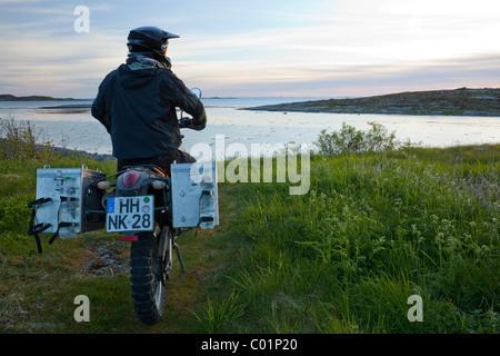 Man riding an Enduro motorcycle in the evening twilight, Gimsefjorde, Norway, Scandinavia, Europe - Stock Photo