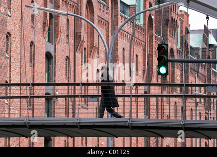 Pedestrian bridge with traffic lights in the Speicherstadt historic warehouse district in Hamburg, Germany, Europe - Stock Photo