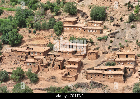 Typical Berber village with traditional adobe houses and small kasbahs in the mountains of the High Atlas, Morocco, - Stock Photo