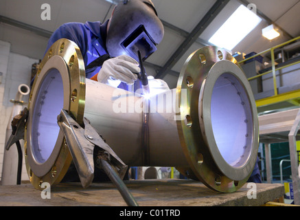 Welder working on pipe junction - Stock Photo
