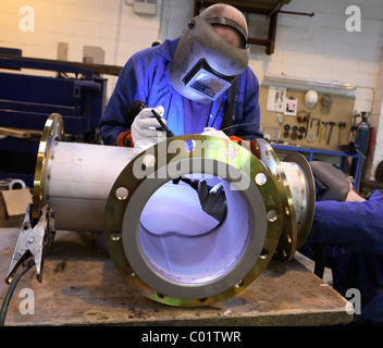 Two welders work together on pipe work - Stock Photo