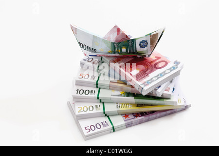 Stacked euro notes in bundles with boat made from notes - Stock Photo