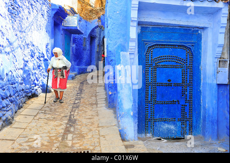 An old woman walking in a narrow alley with blue painted walls and doors in the Medina, old town, Chefchaouen, Rif - Stock Photo