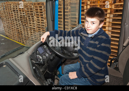 A MODEL RELEASED eleven year old boy sits in a HGV lorry cab in the Uk - Stock Photo