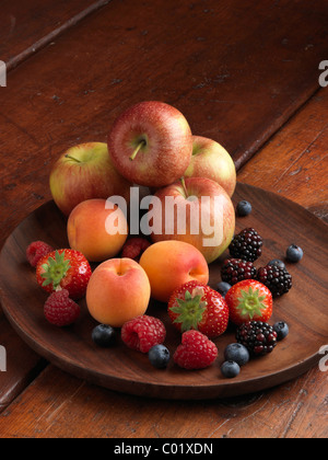 A pile of fresh ripe fruit apples strawberries blueberries blackberries raspberries and apricots - Stock Photo